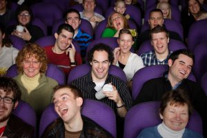 A large audience in a darkened movie theater.
